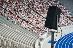 Loudspeaker in stadium. Closeup of loudspeaker in sports stadium with crowd and running track in background stock photo