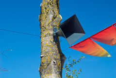 The loudspeaker on tree on background of blue sky and red holiday flags Stock Images