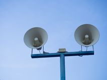 Loudspeakers against on blue sky background. Stock Photos