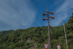 Loudspeakers broadcast tower with a blue sky and Mountain background . Loudspeakers broadcast tower with a blue sky and Mountain background Stock Photo
