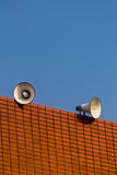 Loudspeakers on builing and blue sky background Stock Photos