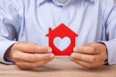 Louez ou achetez une maison L'homme tient la maison rouge avec le coeur photographie stock libre de droits