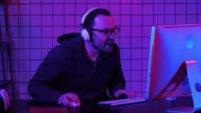 Lough diabolico del gamer arrabbiato mentre giocando sul computer Gamer impressionabile archivi video