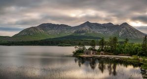Lough Inagh in Ireland with a cabin and boats at the lake shore. Beautiful lake called Lough Inagh in County Galway, Ireland with a cabin and boats at the lake stock images