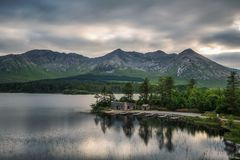 Lough Inagh in Ireland with a cabin and boats at the lake shore. Beautiful lake called Lough Inagh in County Galway, Ireland with a cabin and boats at the lake royalty free stock photography