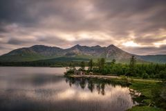 Lough Inagh in Ireland with a cabin and boats at the lake shore. Beautiful lake called Lough Inagh in County Galway, Ireland with a cabin and boats at the lake stock photo