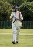 Man walking out to bat at local charity cricket match stock images