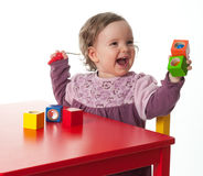 Loughing child with building bricks. A loughing child playing with building bricks Stock Photos