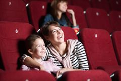 Loughing mother and daughter at the cinema Stock Photo
