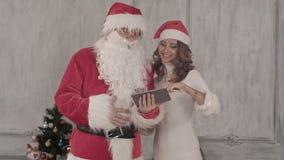 Loughing Santa και όμορφη ταμπλέτα χρήσης γυναικών απόθεμα βίντεο