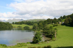 Loughrigg Tarn. Beautiful Loughrigg Tarn in The English Lake District National Park with the Langdale Peaks in the Distance Royalty Free Stock Image