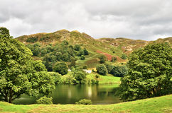 Loughrigg tarn, English Lake District. Cumbria, England, a natural lake nestling in the mountains in a hollow cirque formed by ancient glaciers Royalty Free Stock Photo