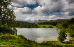 Loughrigg Tarn in Lake District. Sun illuminating Langdale Pikes with Loughrigg Tarn in foreground Royalty Free Stock Photo