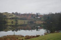 Loughrigg Tarn: litet bergsjö och lantgårdhus med perfekta reflexioner i sjöområdet Cumbria arkivfoto