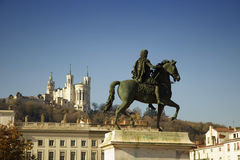 Louis XIV equestrian statue at Bellecour square. Louis XIV equestrian statue located at the center of the Bellecour square in Lyon, France.  Fourviere basilica Royalty Free Stock Image