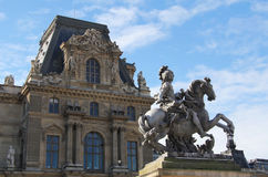 Louis XIV statue with Louvre palace Stock Photos