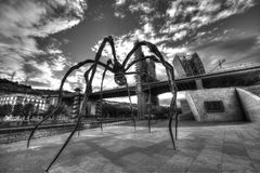 Louise Bourgeois spider in Bilbao, spain. Spider statue called `Maman` created by Louise Bourgeois and located in Bilbao, Spain, with La Salve bridge in the Royalty Free Stock Images