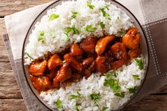 Louisiana food: bourbon chicken with garnish of rice close-up se. Rved on a plate on the table. horizontal top view from above, rustic royalty free stock image