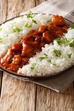 Louisiana food: bourbon chicken with garnish of rice close-up se. Rved on a plate on the table. vertical, rustic royalty free stock images