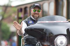The Pegasus Parade 2018. Louisville, Kentucky, USA - May 03, 2018: The Pegasus Parade, Man riding motorcycle waving for the camera royalty free stock image