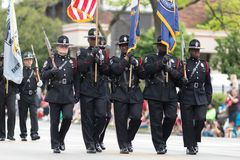 The Pegasus Parade 2018. Louisville, Kentucky, USA - May 03, 2018: The Pegasus Parade, Police Officers carrying rifles, scorting the American flag stock images