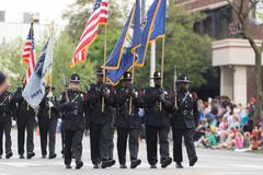 The Pegasus Parade 2018. Louisville, Kentucky, USA - May 03, 2018: The Pegasus Parade, Police Officers carrying rifles, scorting the American flag royalty free stock photo