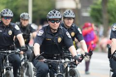 The Pegasus Parade 2018. Louisville, Kentucky, USA - May 03, 2018: The Pegasus Parade, Police Officers riding bicycles down W Broadway stock image