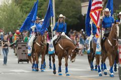 The Pegasus Parade 2018. Louisville, Kentucky, USA - May 03, 2018: The Pegasus Parade, Women dress up as cowgirls riding horses carrying flags down W Broadway royalty free stock image