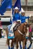 The Pegasus Parade 2018. Louisville, Kentucky, USA - May 03, 2018: The Pegasus Parade, Women dress up as cowgirls riding horses carrying flags down W Broadway stock images
