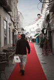 Loule, Portugal - 7 December, 2016: man walking on red carpet in town street with christmas decoration Stock Photo