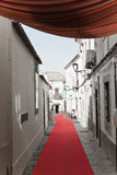 Loule, Portugal - 7 December, 2016: walking on red carpet in town street with christmas decoration. Enjoying shopping in narrow town street with red carpet and Stock Photography