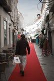 Loule, Portugal - 7. Dezember 2016: bemannen Sie das Gehen auf roten Teppich in der Stadtstraße mit Weihnachtsdekoration Stockfoto