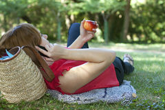Lounch break in aearly autumn park. Red-haired woman laying with apple and talking on the phone Royalty Free Stock Photography