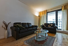Lounge. Living room with wood imitation laminate floor and leather sofas Stock Images