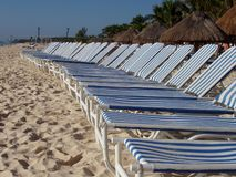 Lounge on beach. Empty beach chairs in front of tiki huts Stock Images