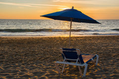 Lounge on the beach. Lounge chair and umbrella on restful beach in the sunset with copyspace Royalty Free Stock Photos