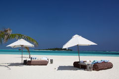 Lounge beds. With parasols on the beach Stock Photos