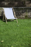 Lounge chair. On the grass, front of stone wall Royalty Free Stock Photos