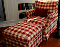 Lounge chair. Comfortable lounge chair and ottoman in red and white plaid royalty free stock photos