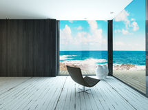Lounge chair against huge window with seascape view royalty free stock images
