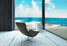 Lounge chair against huge window with seascape view Royalty Free Stock Image