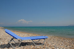 Lounge chair at beach. A view of a blue striped lounge chair on a vacant pebble beach, next to the water on a hot summer day at the Gulf of Corinth Stock Photos