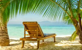 Prepared for relaxation at the beach. Lounge chair on the beach, in the shade of a palm tree leaf Royalty Free Stock Image