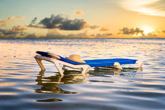 Lounge Chair in the Ocean with Hat Resting on Top Stock Photo