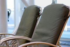Lounge chairs. Two green chairs sitting by the side of an indoor pool Stock Photos