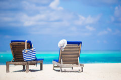 Lounge chairs with bag and hat on tropical beach Stock Image