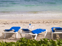 Lounge Chairs on the Beach. Blue and white lounge chairs on the beach Stock Photo