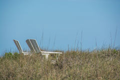 Lounge chairs on the beach dunes Royalty Free Stock Images