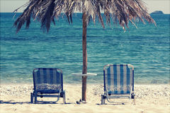 Lounge chairs on the beach - retro style photo Stock Photo
