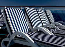 Lounge chairs on a cruise ship. A row of lounge chairs sitting in the sun on a cruise ship Stock Image